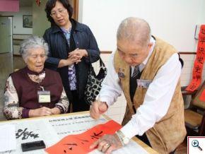 張國安師伯一筆一畫的為菊花婆婆寫下新年快樂的日語祝福的春聯