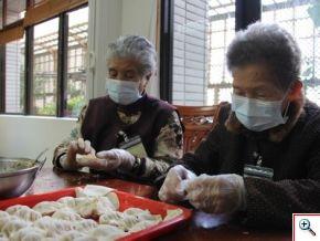 輕安居奶奶們認真地包著水餃,一顆顆飽滿的餃子在她們熟練的手中成形