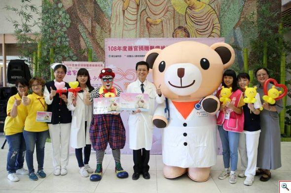 花蓮慈濟醫院副院長陳培榕(右五)與小麥貝兒熊(右四)、小丑熊熊(左五)及器捐宣導團隊邀約民眾一起來簽署器官捐贈同意書